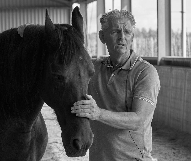 Jan staat naast een paard en houdt haar hoofd en nek vast. Ze staan in een paardenbak tijdens paardencoaching.